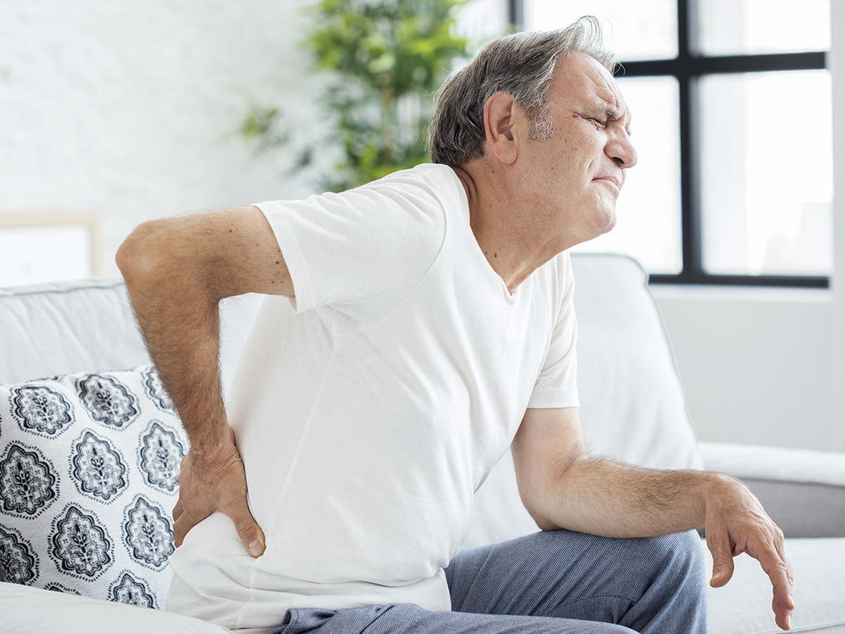 Image of an older man holding his lower back in pain
