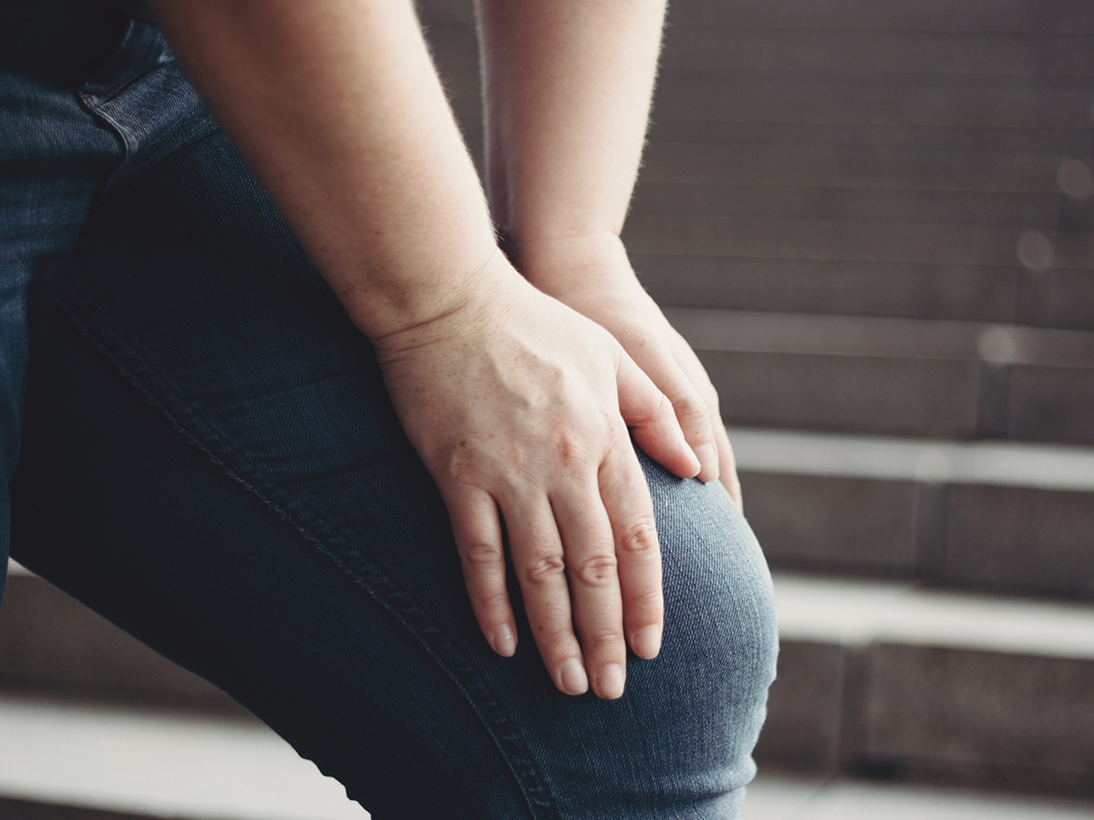 Image of a person clutching their injured knee.