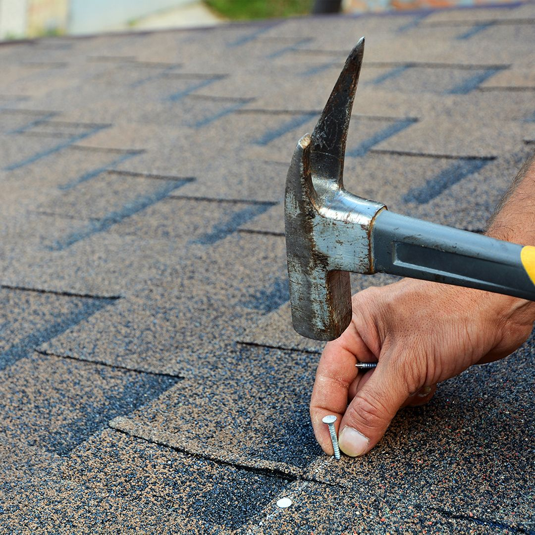 roofer hammering nails into shingles