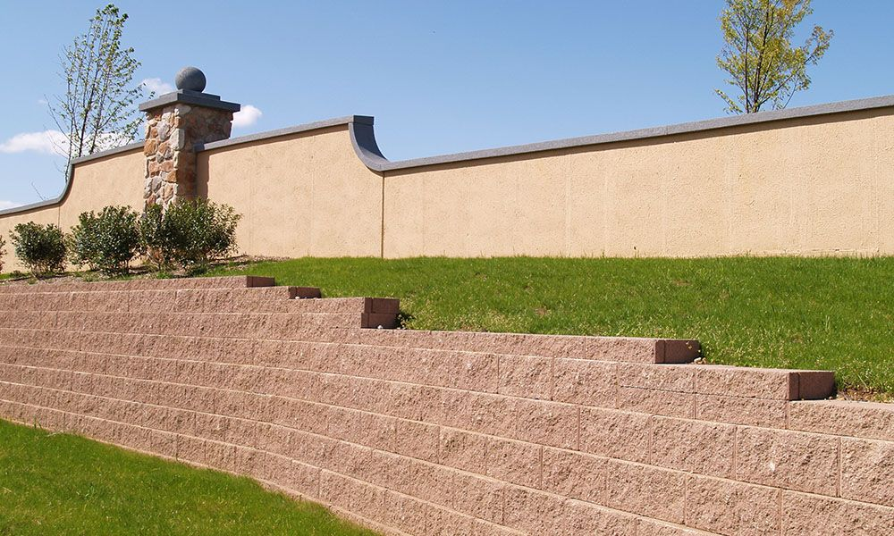Brick retaining wall with grass and bushes.