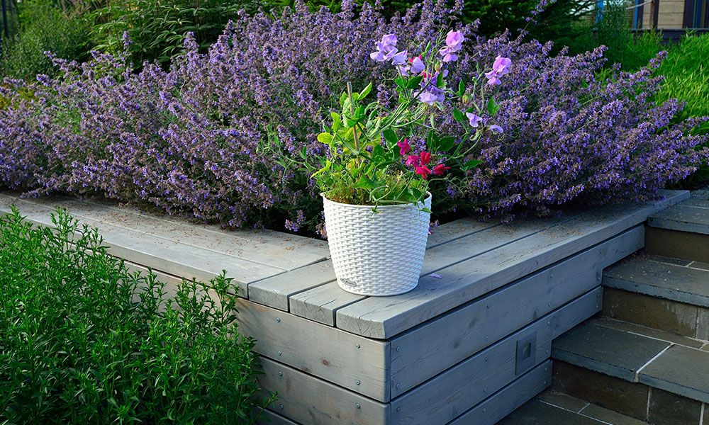 Retaining wall with steps next to it and a planter of flowers on top.
