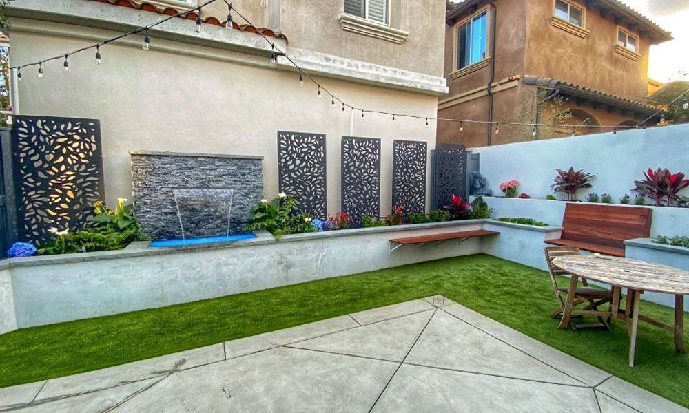 Backyard with a concrete patio and a retaining wall with a water feature.