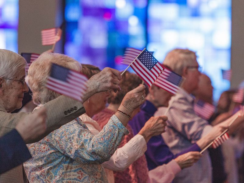 A crowd of people waving American flags.