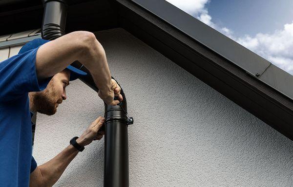 A man fixes a home's gutter system.