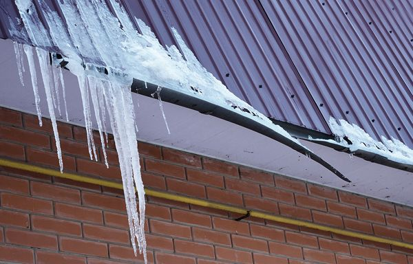 A gutter system broken and covered in ice.