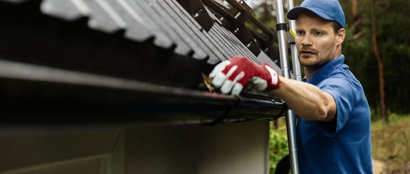 A worker cleaning house gutters.