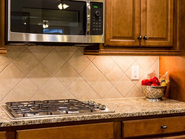 A new gas cooktop on a granite countertop with a tile backsplash