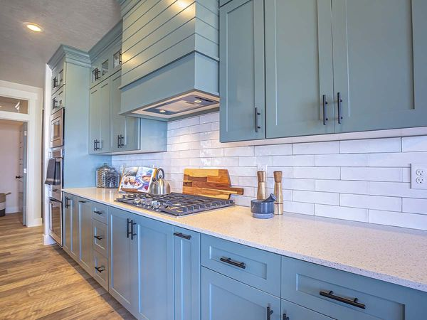 Kitchen with white countertop and bluish-gray cabinets against tile backsplash