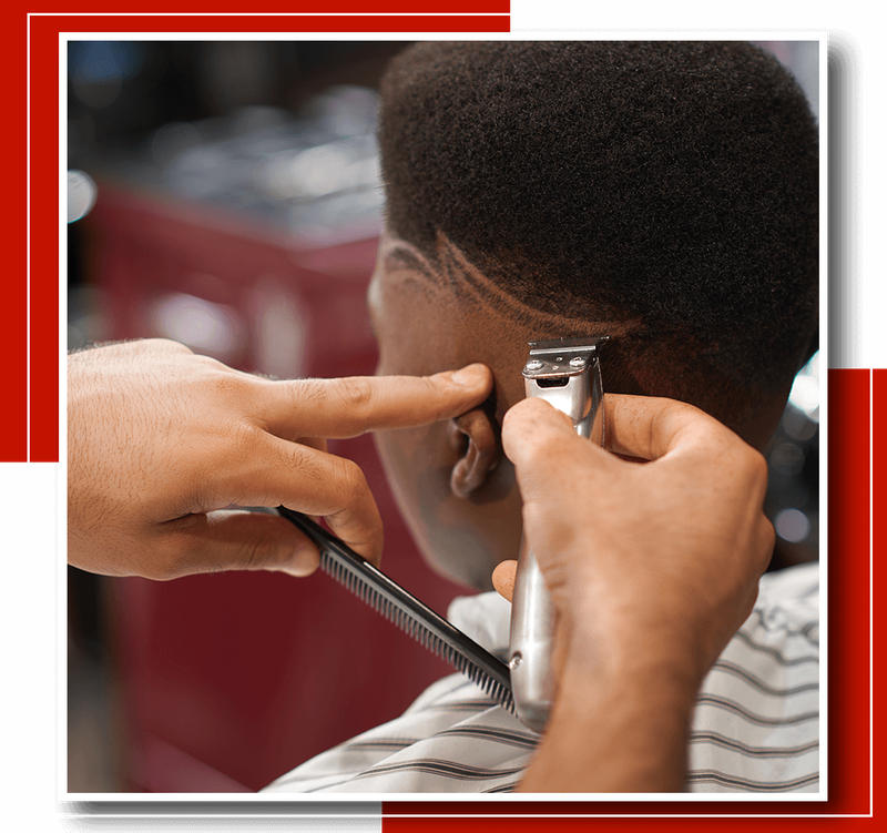 Closeup of process of trimming trendy stripes on head in barber shop.