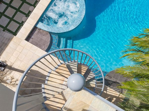 Top-down image of an exterior spiral staircase and outdoor pool