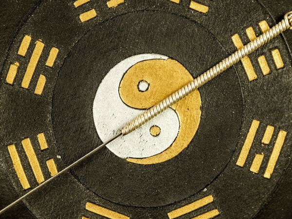 Acupuncture needle on Chinese Taoism symbol in a closeup