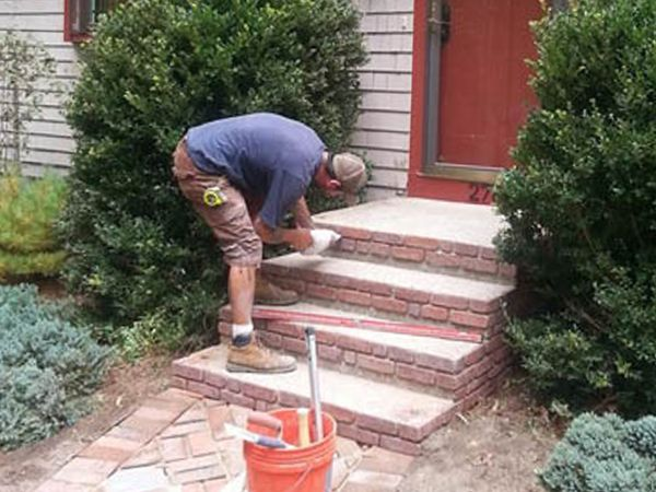 Image of a Well Done Landscapes worker performing masonry repair in Lakeville.