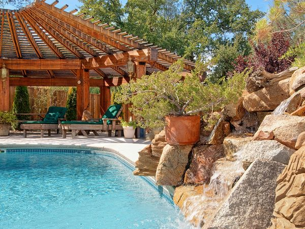 Image of a backyard swimming pool with a large rock feature featuring a waterfall.