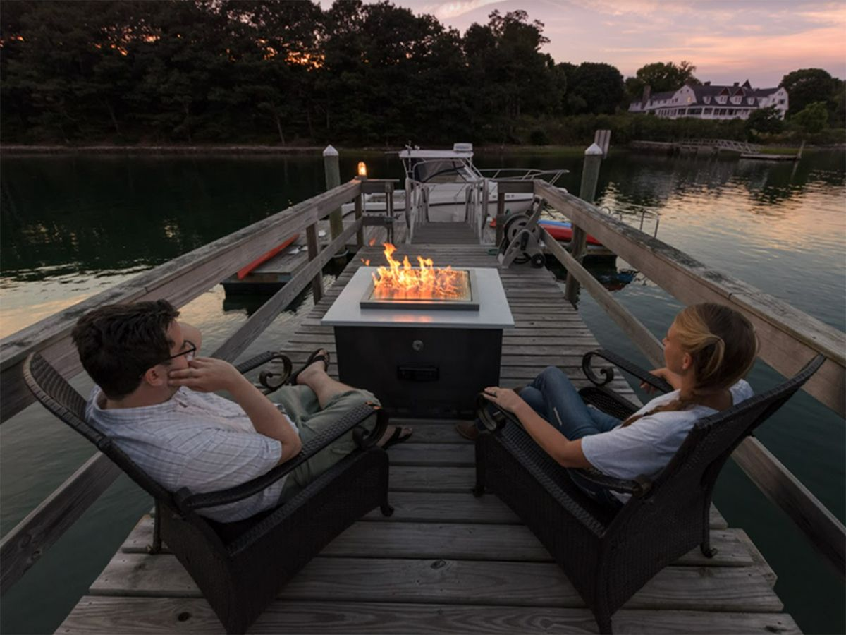 Image of a couple relaxing near a fire pit, on a dock over a lake.