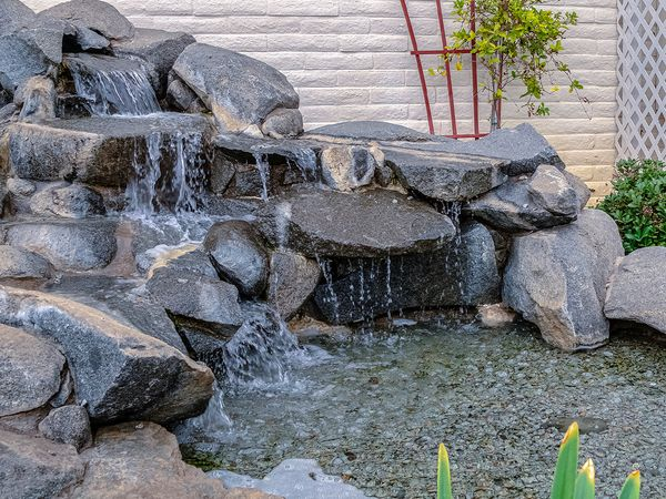 Image of a custom backyard water feature with a stone cascade waterfall.