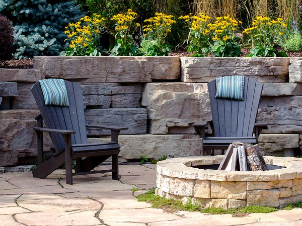 Image of a backyard patio with two chairs and a fire pit.