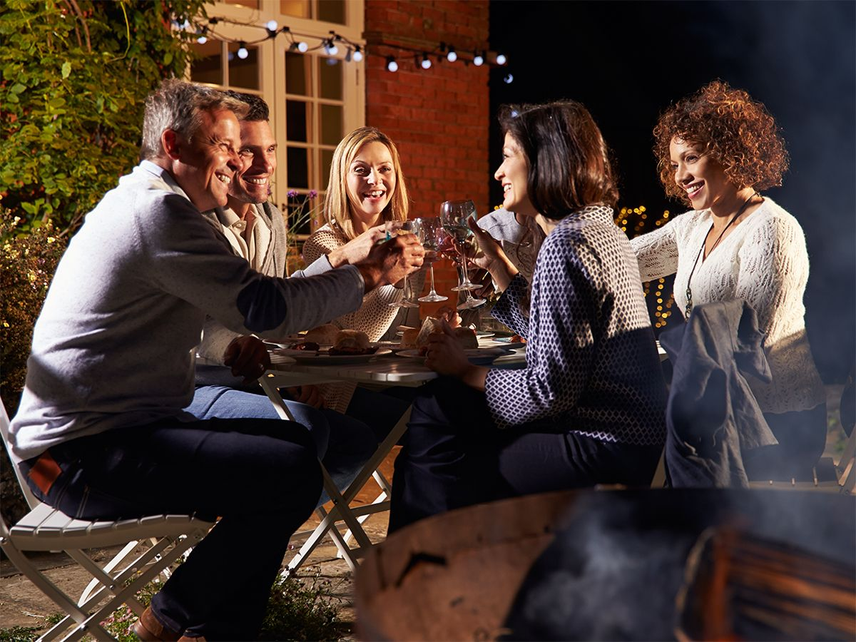 Image of a group of friends enjoying an outdoor meal near a fire pit.