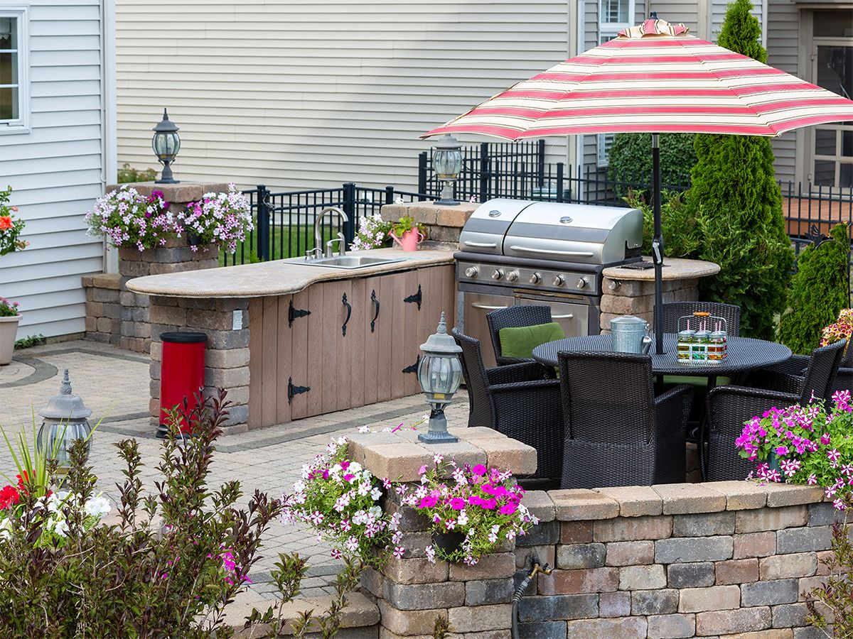 Image of a luxurious outdoor kitchen area with a sink, grill, and table.
