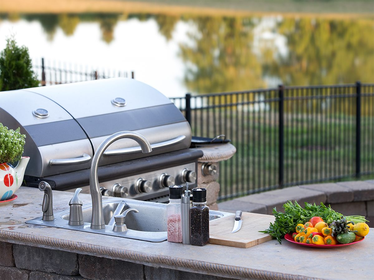 Image of an outdoor kitchen area with a sink and a grill.