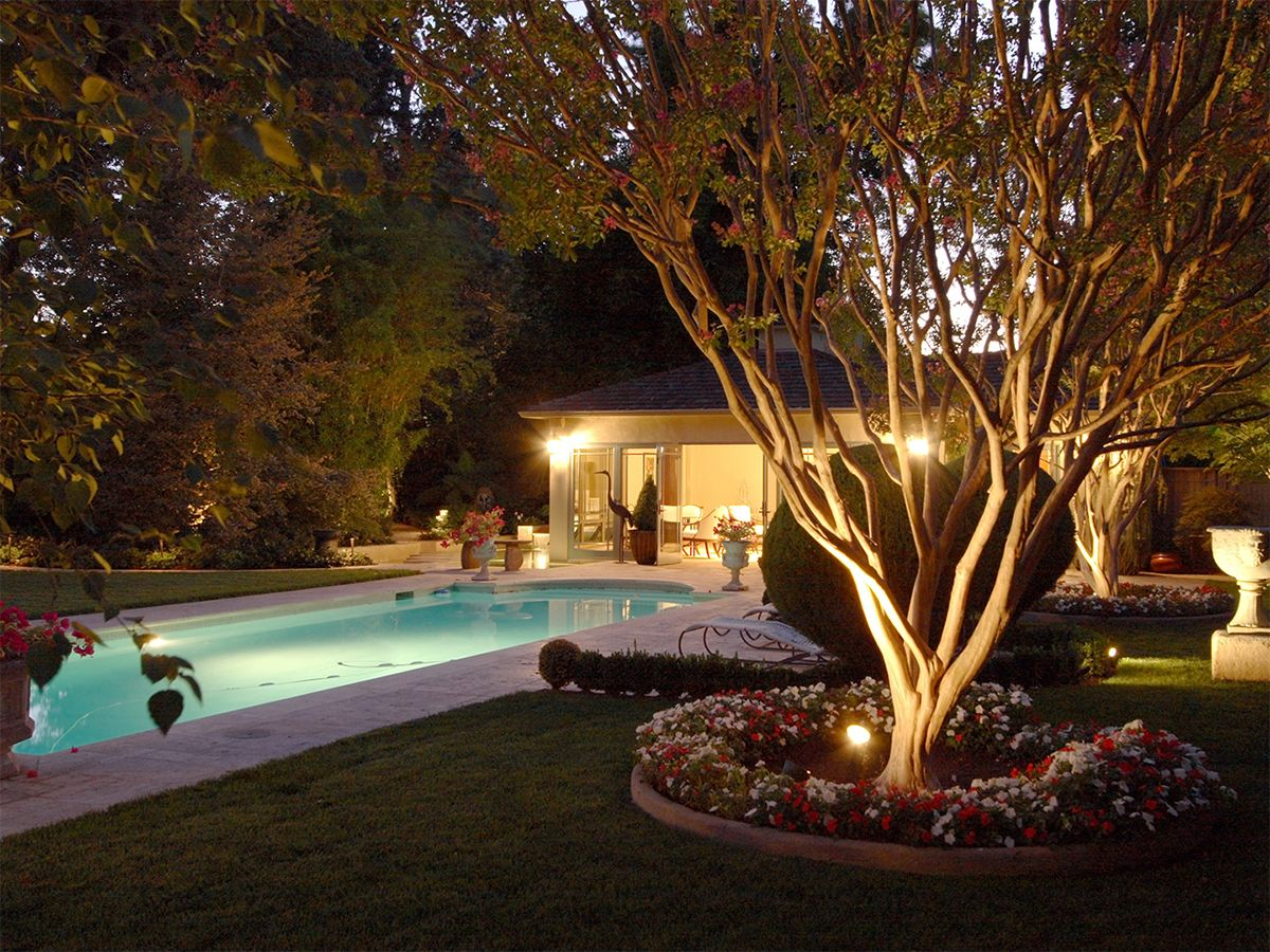 Image of a luxurious backyard featuring a swimming pool and an outdoor lighting system.