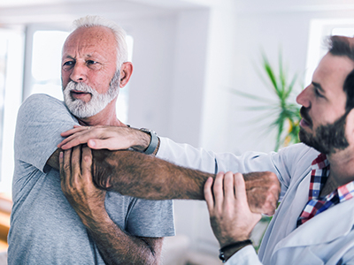 Older Man receiving physical therapy on his shoulder