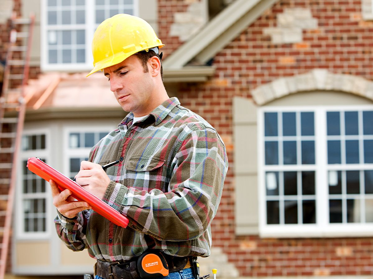 worker in a hard hat taking notes before working on a home's roof