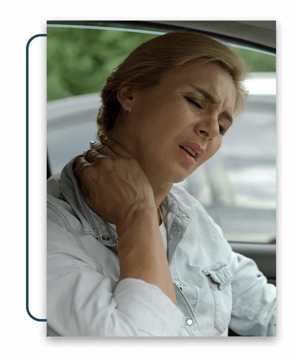 Woman sitting in her car, holding her neck in pain.