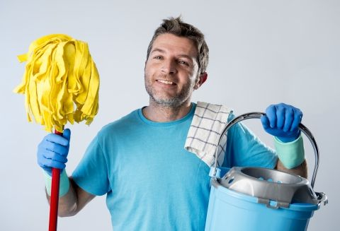 Man smiling while holding mop and bucket