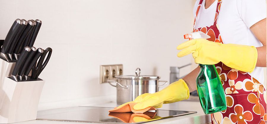 cleaning kitchen stove top with spray bottle