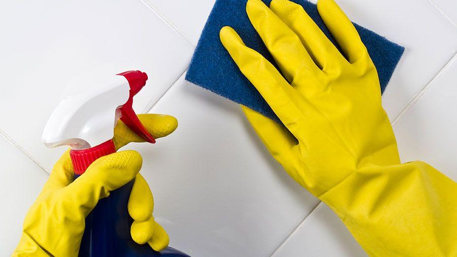 scrubbing tile surface spray bottle yellow gloves