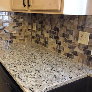 Image of granite countertop with custom tiling and cabinetry