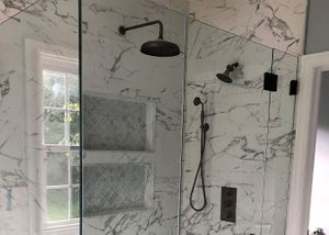 Close up of marble shower with overhead shower head