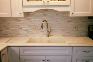 Close up of remodeled kitchen sink with gold sink head