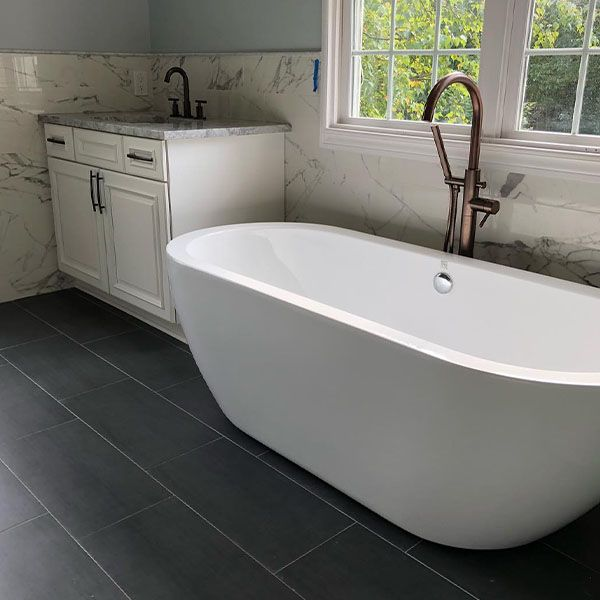Image of remodeled bathtub with dark gray tiling