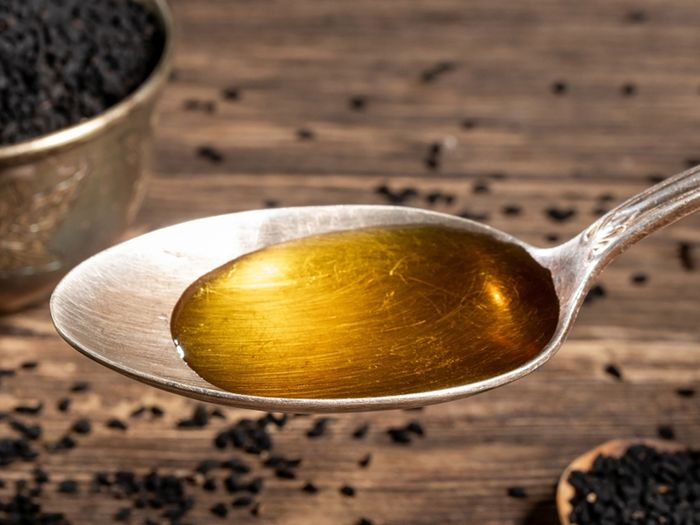 Black seed oil in a spoon.