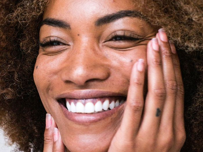 close up of a smiling woman with her hands near her face