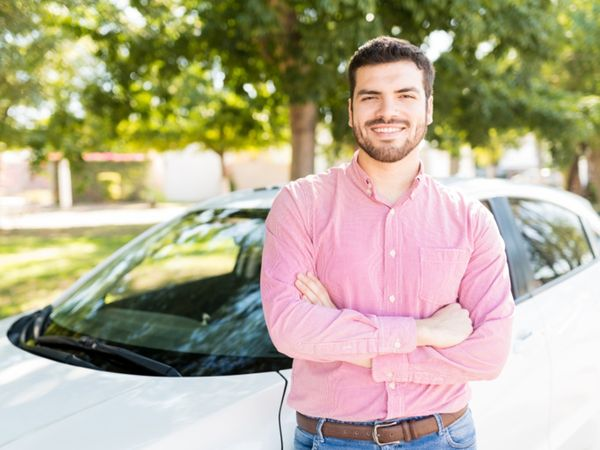 Man standing next to a white, four-door vehicle.