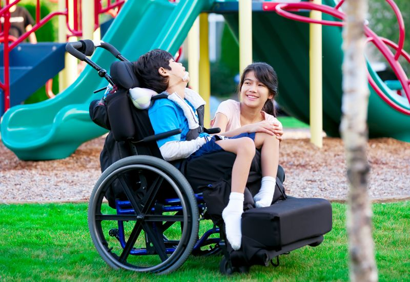 sister and brother in wheelcheer in a park.jpg