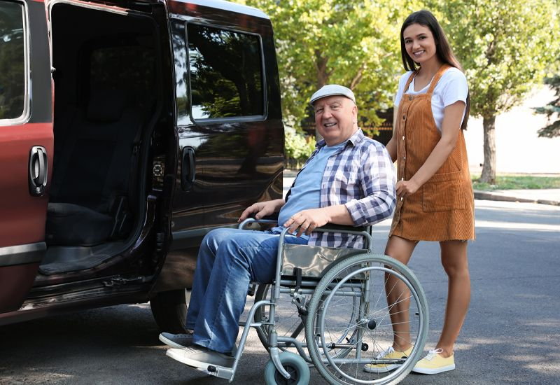 daughter and father in wheelchair next to van.jpg