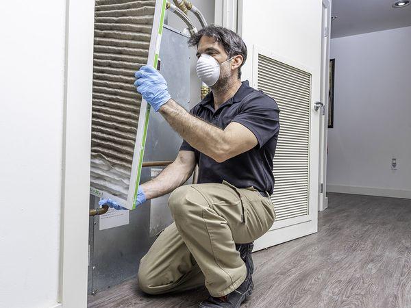 An HVAC technician holding a dirty air filter.