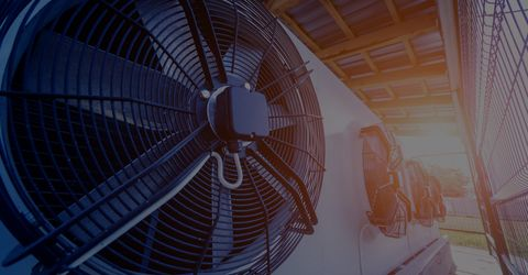 Fans that make up an industrial air conditioning unit outside with bright light shining through the corner of the image.