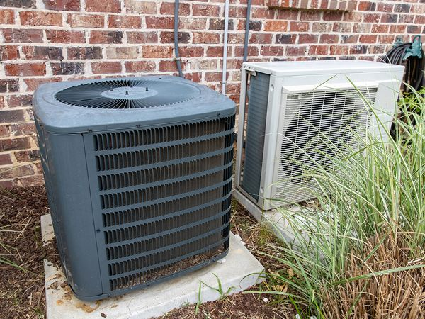 An outdoor air conditioning unit that is dirty with leaves.