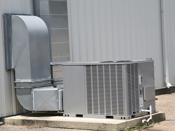 An outdoor commercial air handling unit connected to a large commercial building.