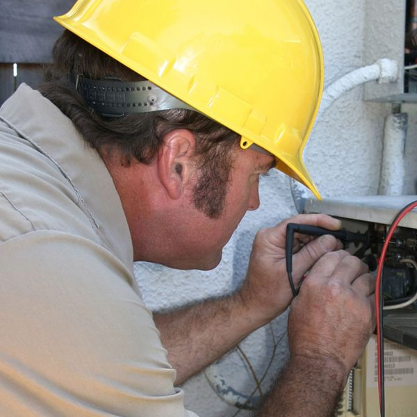 A repair man wearing a yellow helmet testing the voltage on a compressor unit.