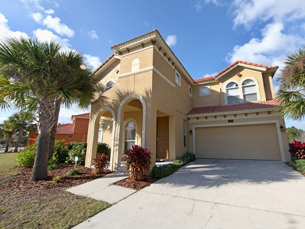 The exterior of a Florida home with large palm trees out front.