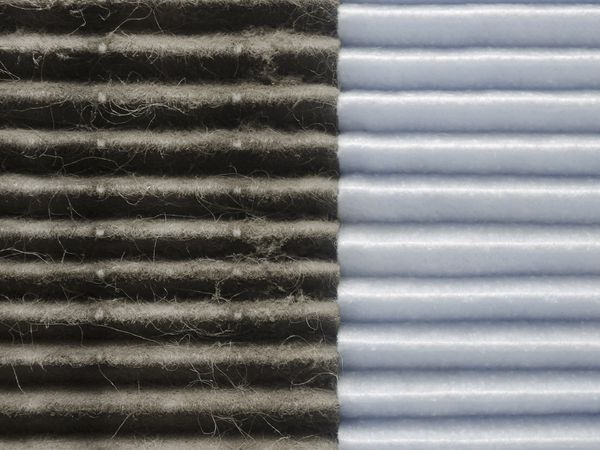 An up close look at an air filter that is half dirty and half clean.
