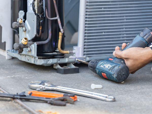 An HVAC technician working on an outdoor HVAC unit.