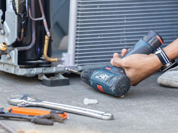 Technician using a drill to fix a modern AC system.