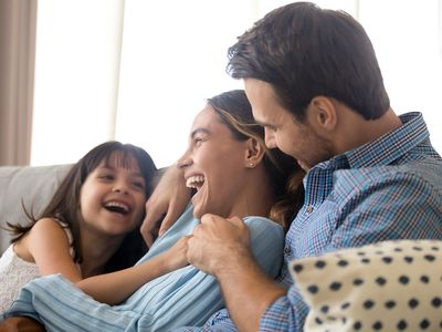 Happy family smiling on the couch.