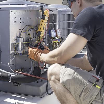 Man performing repairs on a broken air conditioner.